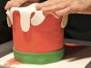Stendere la pasta di zucchero verde e ritagliarla per creare il bordo alla base della candela.