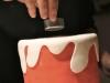 Dopo aver steso la pasta di zucchero bianca e ritagliato i contorni frastagliati, ad imitare la cera di una candela, coprire la parte superiore e praticate il foro per l\'inserimento della candela. Accendete la