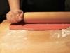 Ammorbidire la pasta di zucchero rossa (in vendita on line e nei negozi di cake design) e con l'aiuto di un mattarello, stenderla su una superficie spolverizzata di zucchero al velo onde evitare che si attacchi.